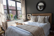 An eclectic bedroom with dark gray walls and a convex mirror