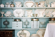 A collection of serving pieces on light-blue shelves