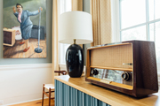 A detail of a vintage radio and a black table lamp.