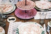 Colorful floral-patterned place settings surrounding a three-tiered serving tray