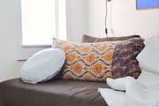 Patterned decor pillows sitting beside a fringe throw blanket.