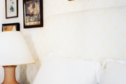 A white headboard against yellow patterned wallpaper