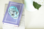 A vase of hydrangeas next to a gray box, purple book, and turquoise skull
