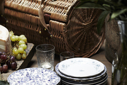 Small plates and round picnic basket atop wooden table.