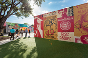 Outdoor-museum visitors parading past socially conscious themed murals