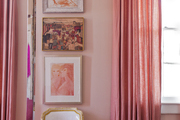 A French-style accent chair beside pink curtains