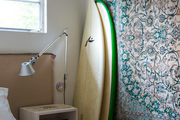 A detail of surfboards leaning on a wall covered in a hanging rug.