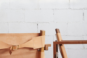 Details of two wood-and-leather arm chairs designed by Friends & Family