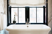 A white freestanding tub beside a window in a marble bathroom