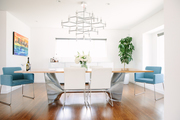A sleek dining table with a silver base and blue accent chairs beneath a modern chandelier.