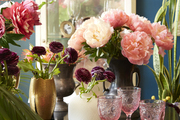 Pink peonies, glassware, and other assorted flowers on a dining table.