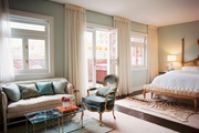 A sitting area with a beige settee and french doors in a master bedroom