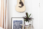 A guitar and hat float above a framed map