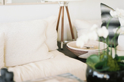 A white couch beside a tripod table lamp