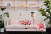 A retail store with a pink sofa and white walls.