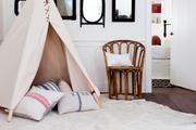A tepee filled with pillows atop a hide rug