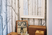 Tree-trunk wallpaper and a white mirror in a bathroom nook