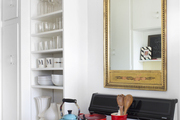 Colorful cookware set off by a mirror and open shelving for glassware and white dishware