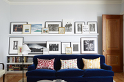 Blue sofa with colorful throw pillows front of picture covered shelves.