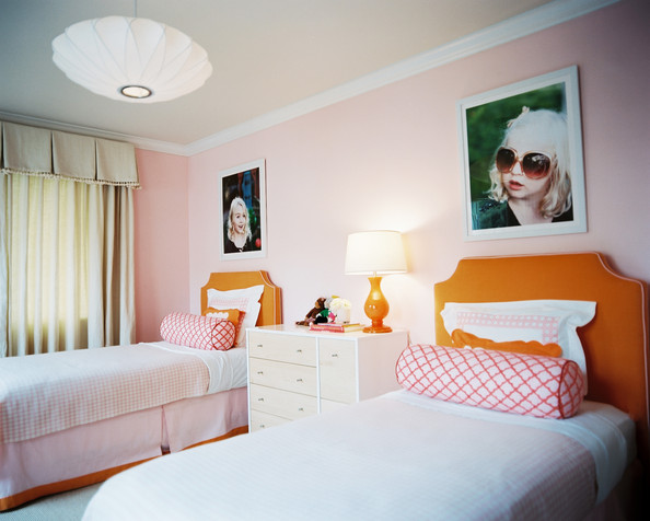 Pink Kids' Room - Large-scale photographs above orange upholstered headboards and pink bolster pillows