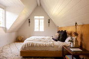 A bohemian bedroom with an a-frame ceiling