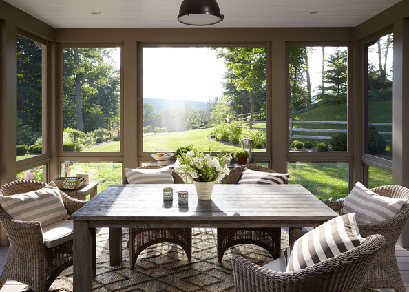 Porch - A wooden dining table surrounded by rattan chairs in a screened-in porch
