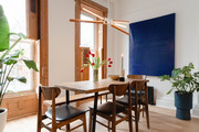 Eclectic dining room with modern light fixture and indigo tapestry.