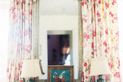 Floral curtains and a pair of lamps flanking a mirror