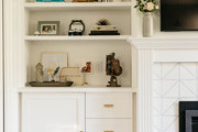 A white bookshelf beside a fireplace with white tile.