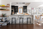 This kitchen and dining area features a marble island with bar stools.