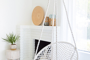 A white hanging chair in a contemporary living room with bohemian accents.