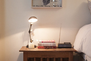 A wooden nightstand topped with a task lamp