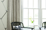 Striped white and black chairs behind large white windows.