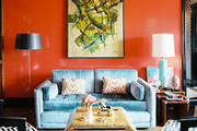 Red lacquered walls and a blue couch on herringbone hardwood floors
