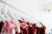 A detail of dresses hanging on a rack.