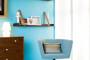 Sustainable mango-wood belt shelves against a teal-hued wall at Jessica Alba's Honest Company office