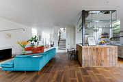 A wood-laden kitchen and a blue sofa set the scene.