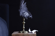 A winged lamp atop a wooden bedside table