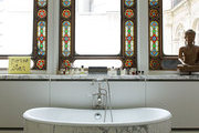 A marble-clad soaking tub on parquet floors beneath stained glass windows