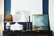 Artwork and candlesticks atop a wooden cabinet with a glass door
