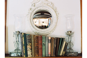 A Federal-style concave mirror above a shelf of books flanked by hurricane lamps