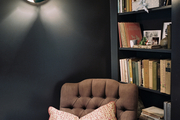 Deep-gray walls and built-in shelving surrounding a tufted armchair