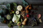 Autumnal fruits and vegetables atop a rustic surface.