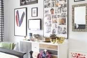 A wall of framed artworks in a gray and white bedroom