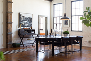 A dining table and chairs under an industrial light fixture in a downtown LA loft
