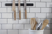 Kitchen utensils displayed on a butcher block counter against subway tile with dark grout.