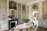 Decorative walls surrounding a dining room with a marble table and a marble fireplace.