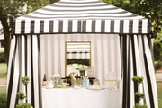 A black-and-white-striped pavilion at an outdoor dinner party