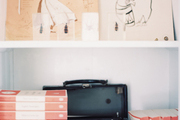 A vintage typewriter and books on a white shelf