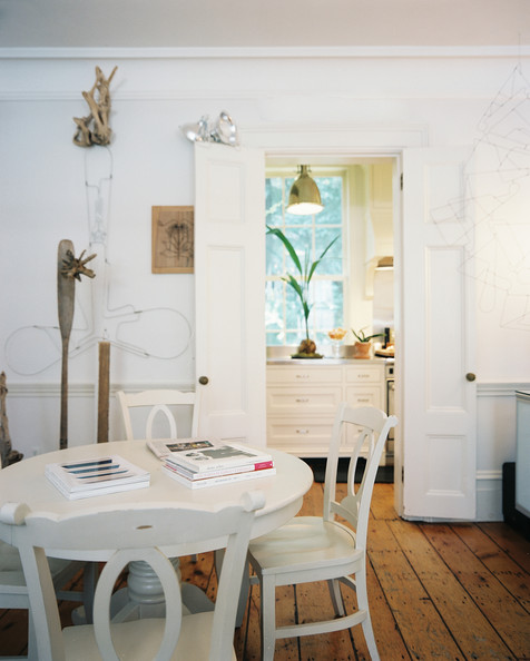 Rustic dining room a white round dining table and chairs atop